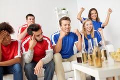 Amis ou passionés du football observant le football à la maison Photographie stock