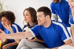 Amis ou passionés du football observant le football à la maison Photo stock