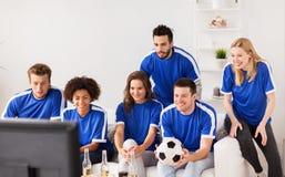 Amis ou passionés du football observant le football à la maison Image libre de droits