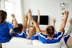 Amis ou passionés du football regardant la TV à la maison Image libre de droits