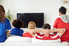 Amis ou passionés du football regardant la TV à la maison Images stock