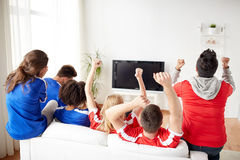 Amis ou passionés du football regardant la TV à la maison Images libres de droits