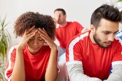 Amis ou passionés du football tristes à la maison Images stock