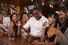 Amis ouvrant le champagne à une nouvelle partie du ½ s de ¿ de Yearï à une barre Photographie stock libre de droits