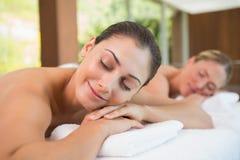 Amis paisibles se trouvant sur des tables de massage Photographie stock libre de droits