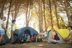 Amis par des tentes au terrain de camping Photos stock