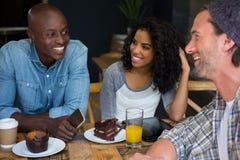 Amis parlant à la table dans le café Photographie stock