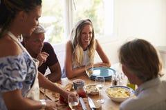 Amis parlant à la table de cuisine tandis que la femme prépare la nourriture Photos libres de droits