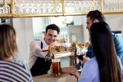 Amis parlant au barkeeper tout en ayant des boissons Images stock