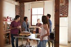 Amis parlant au-dessus du café dans la cuisine, longueur de trois-quarts Images libres de droits