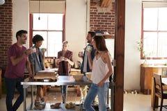 Amis parlant au-dessus du café dans la cuisine, longueur de trois-quarts Image libre de droits