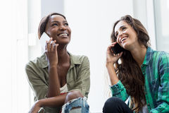 Amis parlant au téléphone portable Photographie stock