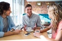 Amis parlant dans le café Photographie stock