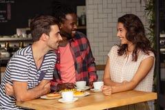 Amis parlant ensemble et souriant Image libre de droits