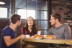 Amis parlant et appréciant le café et des croissants Image stock