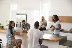 Amis parlant et buvant du café dans la cuisine moderne Images stock