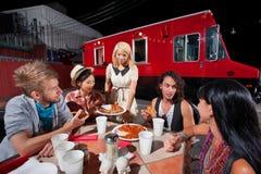 Amis parlant et dinant sur la pizza Image stock