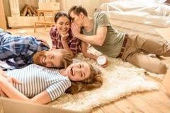 Amis parlant et se trouvant sur le tapis à la nouvelle maison Images stock