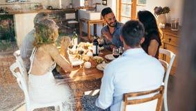 Amis parlant pendant le déjeuner à la maison Photo stock