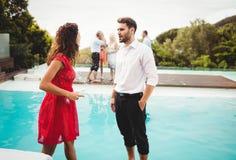 Amis parlant près de la piscine Image libre de droits