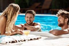 Amis parlant, souriant, cocktails potables, repos, détendant près de la piscine Photographie stock