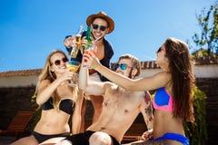 Amis parlant, souriant, cocktails potables, repos, détendant près de la piscine Images libres de droits