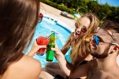 Amis parlant, souriant, cocktails potables, repos, détendant près de la piscine Image libre de droits