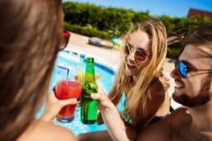 Amis parlant, souriant, cocktails potables, repos, détendant près de la piscine Image stock