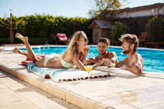 Amis parlant, souriant, cocktails potables, repos, détendant près de la piscine Photos stock