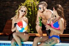 Amis parlant, souriant, cocktails potables, repos, détendant près de la piscine Photographie stock libre de droits