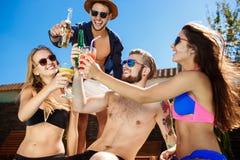 Amis parlant, souriant, cocktails potables, repos, détendant près de la piscine Images stock