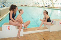 Amis parlant sur le bord de piscine photographie stock