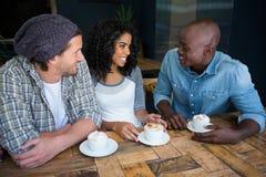 Amis parlant tout en ayant le café à la table dans le café Photographie stock
