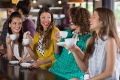 Amis parlant tout en buvant du café en café Photo stock