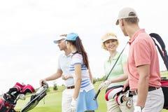 Amis parlant tout en marchant au terrain de golf contre le ciel clair Photo libre de droits