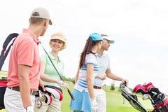 Amis parlant tout en marchant au terrain de golf contre le ciel clair Images stock