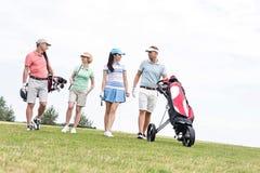 Amis parlant tout en marchant au terrain de golf contre le ciel clair Image stock