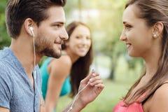 Amis partageant des écouteurs Photos stock
