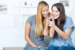 Amis partageant des écouteurs reliés au téléphone portable Image stock