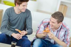 Amis partageant la pizza à la maison Images stock