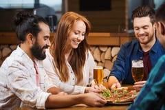 Amis partageant la pizza avec de la bière à la pizzeria Photographie stock libre de droits