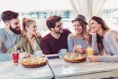Amis partageant la pizza dans un café d'intérieur Photos stock