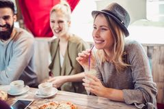 Amis partageant la pizza dans un café d'intérieur Images libres de droits