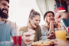 Amis partageant la pizza dans un café d'intérieur Photo libre de droits