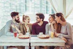 Amis partageant la pizza dans un café d'intérieur Image libre de droits