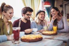 Amis partageant la pizza dans un café d'intérieur Images stock