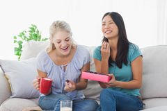 Amis partageant une boîte de chocolats et de rire Photos libres de droits
