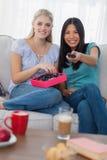 Amis partageant une boîte de chocolats et regardant la TV Photos libres de droits