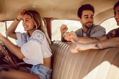 Amis partant en voyage par la route dans la vieille voiture Images stock