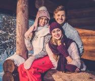 Amis passant des vacances d'hiver sur la maison de montagne Photographie stock libre de droits